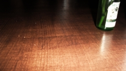 Wooden table with green bottle