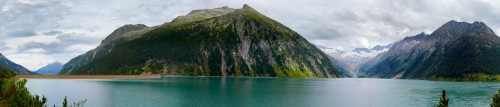 Panoramic view of a dam crest, its storage lake and mountain formations all around; on top cloudy sky